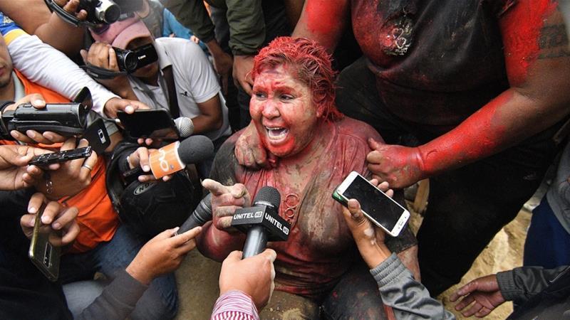 Demonstranten in Bolivia besmeuren burgemeester met rode verf en knippen haar haren af 1
